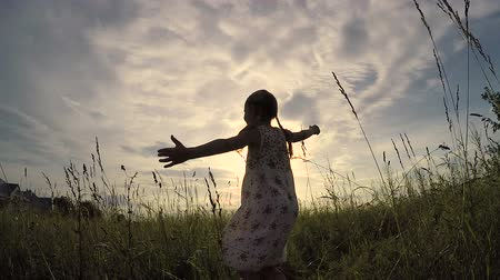 küçük kız : One little girl dancing in the field at the sunset time. Kid having fun outdoors. Concept of happy life.