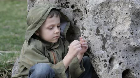 sosyal konular : Sad little boy sitting near the big stone at the day time. Concept of sorrow. Stok Video