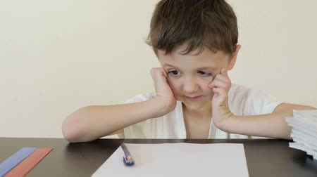 ödev : Sad little boy sitting at the table and doing homework. Concept of bad study.