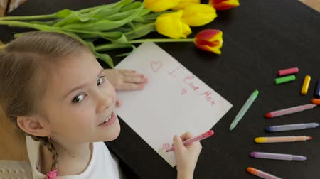 annelik : Happy little girl makes a holiday card for his mom on the table.