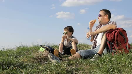 piknik : Father and son sitting in the field at the day time. People having fun outdoors. Concept of friendly family.