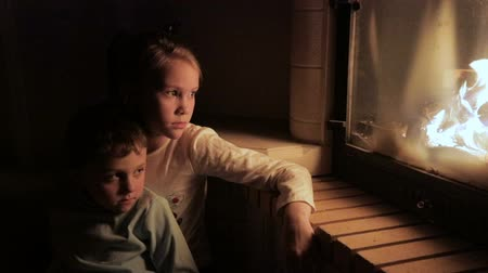 hüsran : Two sad little children sitting by the fireplace and watching the fire. Concept of loneliness Stok Video