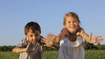 roliço : Two happy children playing in the field at the day time. Kid having fun outdoors. Concept of happy game.