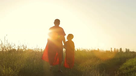 kaland : Father and son playing superhero at the sunset time. People having fun outdoors. Concept of friendly family.