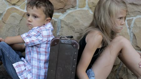 unott : sad brother and sister are sitting by the wall with a suitcase at the day time