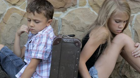 megbocsátás : sad brother and sister are sitting by the wall with a suitcase at the day time