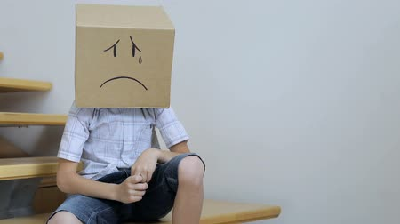 The little boy is sitting on the stairs. He has a cardboard box with different emotions on his head. Stok Video