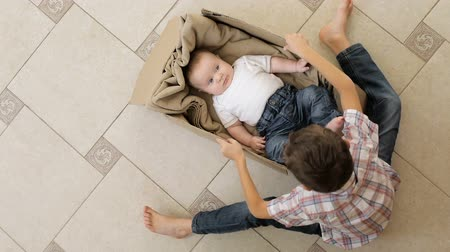 A little boy is playing with his younger brother. He rolls it on the floor in a cardboard box. Concept of happy family. Stok Video