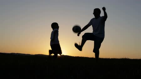 Father and son playing soccer in the park at the sunset time. People having fun outdoors. Concept of friendly family. Stok Video