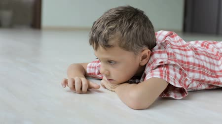 sad little boy lying on the floor at home at the day time