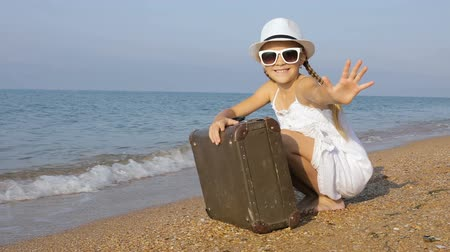 salva : One happy little girl playing on the beach at the day time. Kid having fun outdoors. Concept of summer vacation.