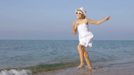 One happy little girl playing on the beach at the day time. Kid having fun outdoors. Concept of summer vacation.