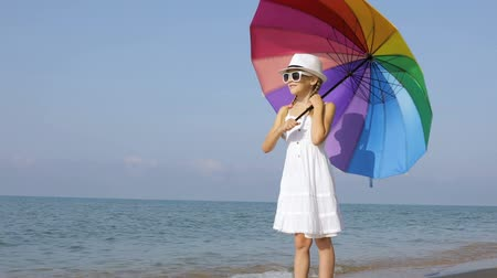 little girl with umbrella standing on the beach.