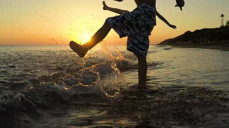 Happy children playing on the beach at the sunset time. Two kids having fun outdoors. Concept of summer vacation and friendly family. Stok Video