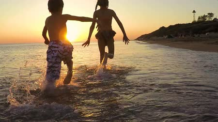 leaping : Happy children playing on the beach at the sunset time. Two kids having fun outdoors. Concept of summer vacation and friendly family. Stock Footage