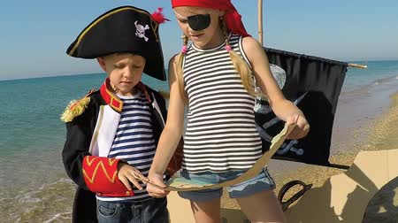 Two happy little children playing on the beach at the day time. They are dressed in sailors vests. Kids having fun outdoors. Concept of sailors on vacation.