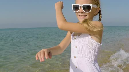 One happy little girl playing on the beach at the day time. Kid having fun outdoors. Concept of happy vacation.