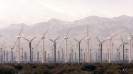 Wind Power 0102: Hundreds of windmills turn in the hazy California desert. Stok Video