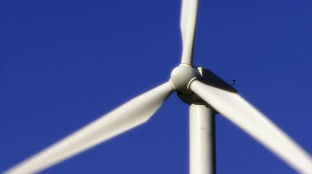 Wind Power 0104: A white wind energy turbine turns against a clear blue sky. Stok Video