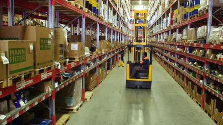 paket : Cardboard boxes inside a storage warehouse. busy worker in a warehouse or factory using a forklift truck to move boxes Stok Video