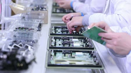 řádek : Workers are manufacturing Circuit Boards in Electronics Factory - Assembly line of LEDs, Transistors and other Electronic components being installed