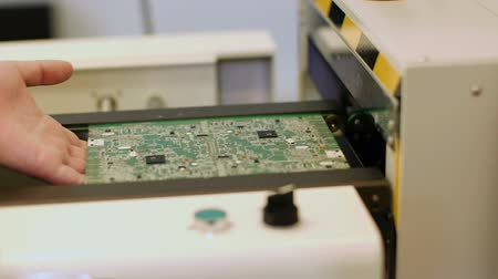 qualidade : Worker controlling quality of PCB boards on production line in factory Stock Footage