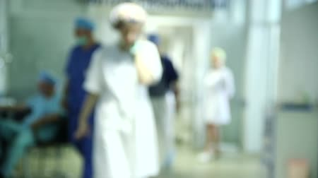 запачканный : medical personal walking in the hall of hospital, unfocused background