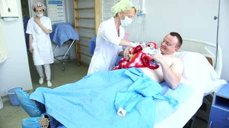 cesarean : father holds his newborn infant for the first time during the skin-to-skin care after Caesarean section