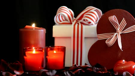 Romantic Valentine gifts with burning candles on black background, zoom in. Стоковые видеозаписи