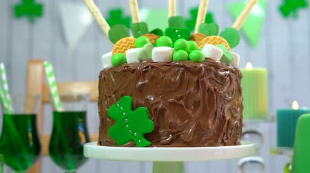 preguiça : Happy St Patricks Day party table with chocolate cake decorated with cookies and candy, closeup on cake.