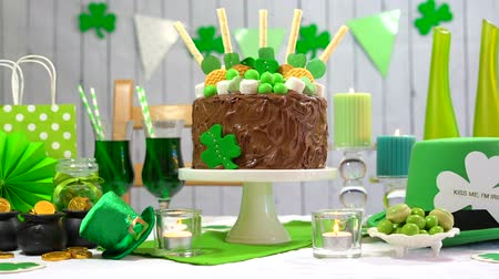 preguiça : Happy St Patricks Day party table with chocolate cake decorated with cookies and candy, full table.