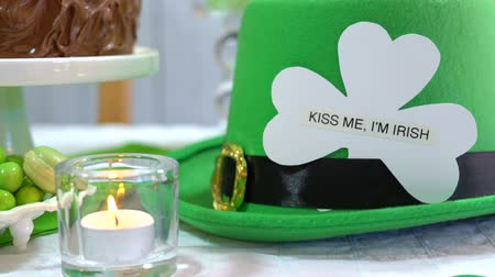 preguiça : Happy St Patricks Day party table with chocolate cake, close up dolly pan to leprechaun with Kiss Me I am Irish greeting message. Stock Footage