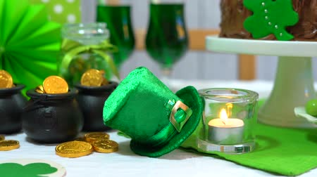 preguiça : Happy St Patricks Day party table with chocolate cake, closeup dolly pan to static on leprechaun hat and pots of gold chocolate.