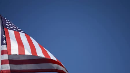 четверть : USA hand flag fluttering in the wind against blue skies.