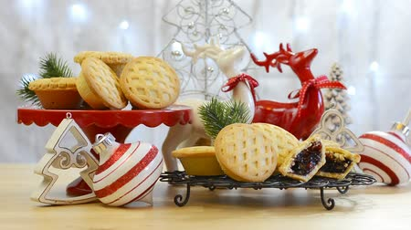 multicor : Festive Christmas food table with English style fruit mince pies and reindeer ornaments centerpeice against a blinking fairy lights background,