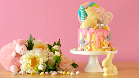 díszített : On-trend Easter theme candy land drip cake decorated with lollipops, cand eggs and white chocolate bunny in party table setting.
