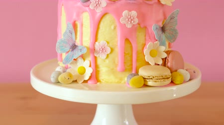 On-trend Easter theme candy land drip cake decorated with lollipops, cand eggs and white chocolate bunny in party table setting.
