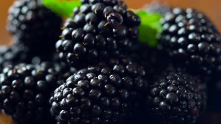 Macro closeup of rotating blackberries summer fruit on dark wood background.