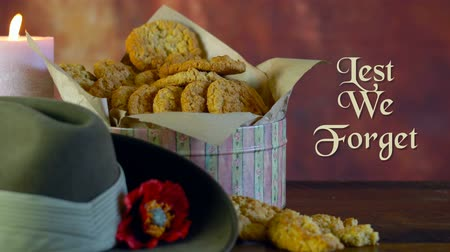 Traditional ANZAC biscuits for ANZAC Day and Remembrance Day memorial holidays in vintage style setting with Lest We Forget animated text greeting message.