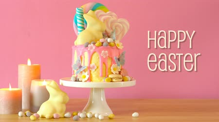 On trend Easter candy land drip cake decorated with lollipops, cand eggs and white chocolate bunny in party table setting, with animated text greeting.