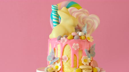 díszített : On trend Easter candy land drip cake decorated with lollipops, cand eggs and white chocolate bunny in pink party table setting.
