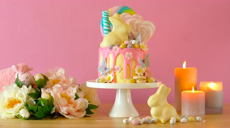 On trend Easter candy land drip cake decorated with lollipops, cand eggs and white chocolate bunny in pink party table setting.