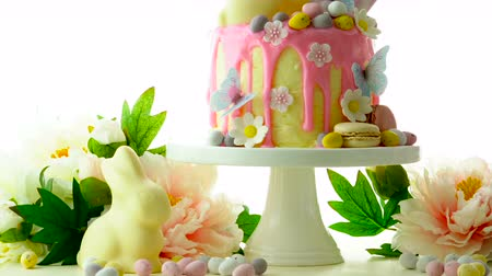 vasárnap : On-trend Easter theme candy land drip cake decorated with lollipops, cand eggs and white chocolate bunny on white background.