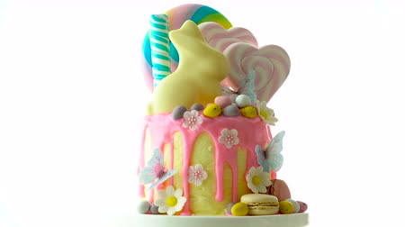 On-trend Easter theme candy land drip cake decorated with lollipops, cand eggs and white chocolate bunny on white background.