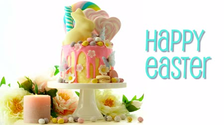 On trend Easter candy land drip cake decorated with lollipops, cand eggs and white chocolate bunny on white background, with animated text greeting.