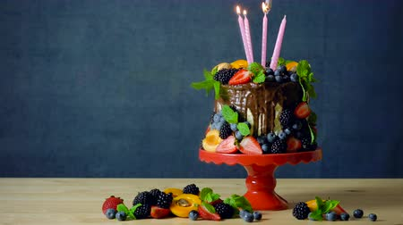 Delicious chocolate drip cake decorated with fresh seasonal fruit and berries with birthday or celebration candles.
