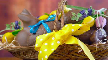 hediyeler : Happy Easter hamper of chocolate eggs and bunny rabbits in large basket with silk tulips on dark wood table, panning macro. Stok Video