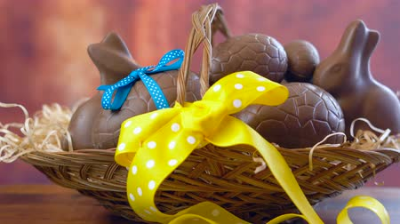 Happy Easter hamper of chocolate eggs and bunny rabbits in large basket with silk tulips on dark wood table, stacking eggs. Стоковые видеозаписи