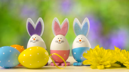 Cute Easter bunny ornaments and Easter Eggs on white table against garden background in the breeze, static.