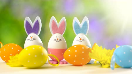 ornamento : Cute Easter bunny ornaments and Easter Eggs on white table against garden background in the breeze, static with lens flare.